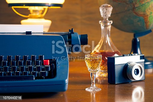 istock Vintage typewriter and camera on a wooden table. Journalism concept 1070440216