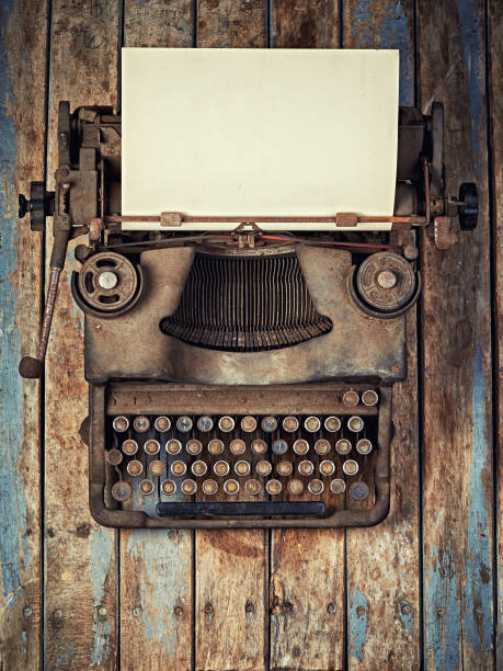 Vintage Typewriter covered with dust on wooden desk topview stock photo