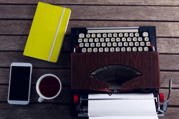vintage schreibmaschine, tagebuch, schwarzen kaffee und smartphone auf holztisch - schwarzer kaffee net stock-fotos und bilder