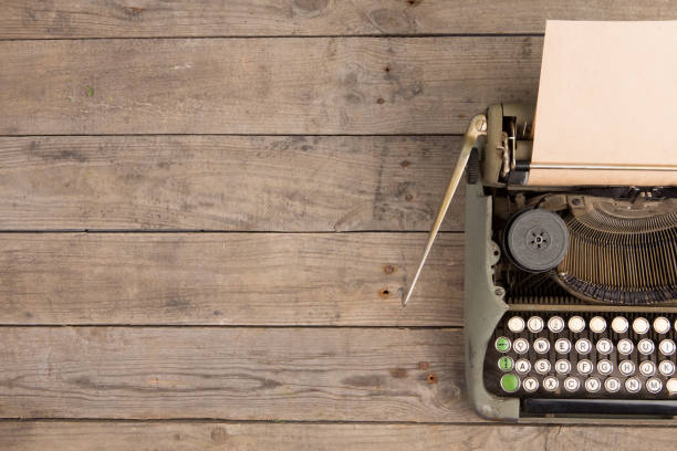 Vintage typewriter on the old wooden desk Vintage typewriter on the old wooden desk copywriter stock pictures, royalty-free photos & images