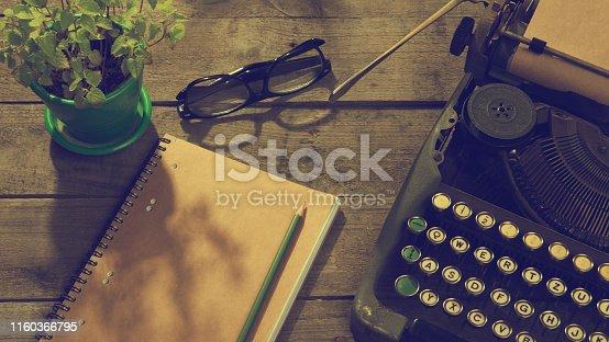 istock Vintage typewriter on the old wooden desk 1160366795