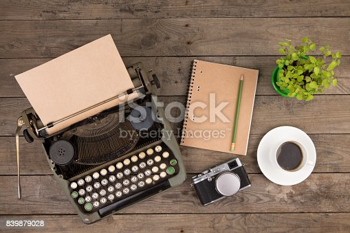 istock Vintage typewriter on the old wooden desk 839879028