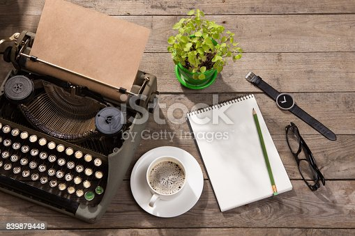 istock Vintage typewriter on the old wooden desk 839879448