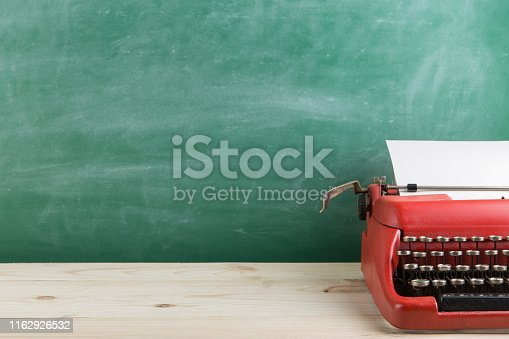 istock vintage typewriter on the table with blank paper - concept for writing, journalism, blogging 1162926532