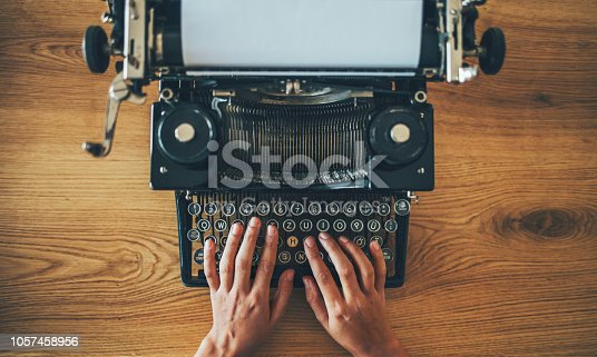 istock Vintage typewriter on writer's desk 1057458956