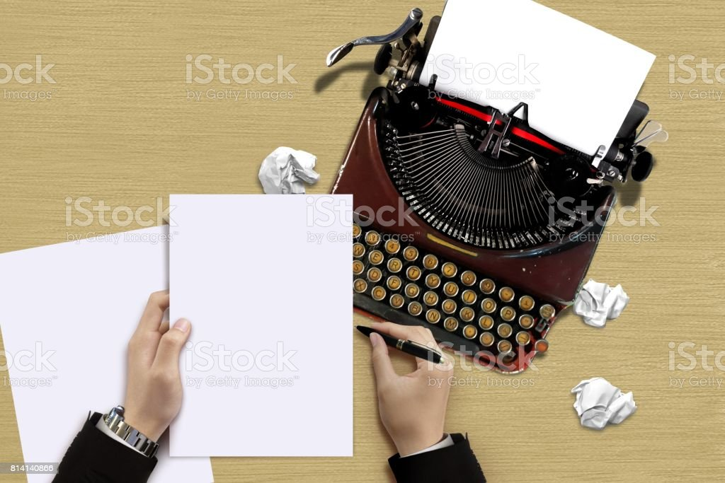 Vintage typewriter with author hand checking a paper sheets stock photo