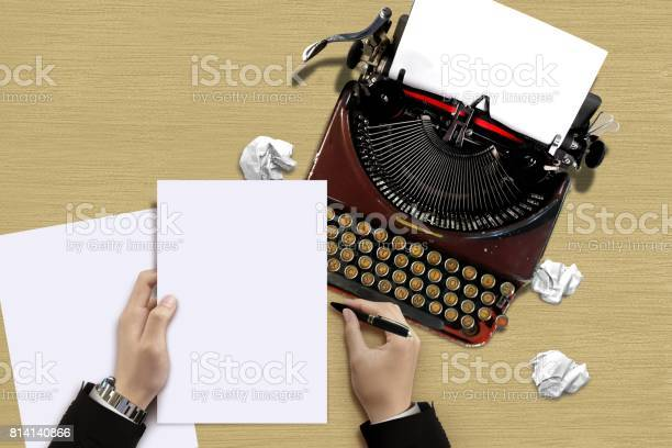 Vintage Typewriter With Author Hand Checking A Paper Sheets Stock Photo - Download Image Now