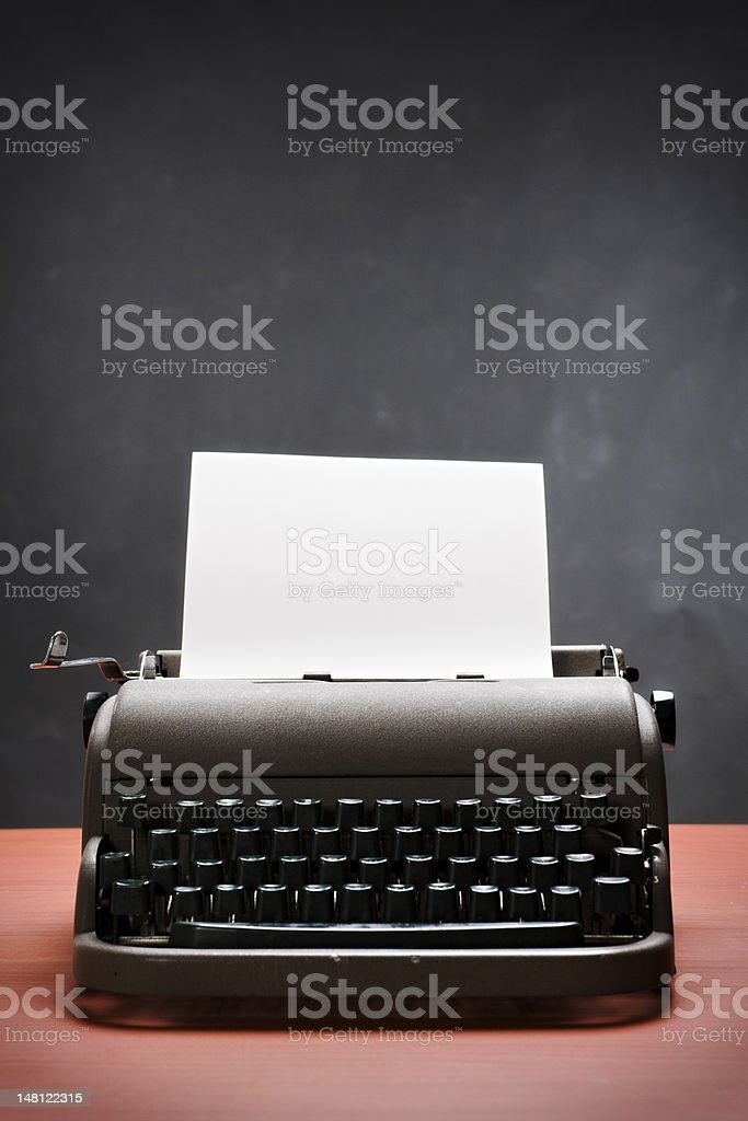 Vintage typewriter with blank paper against grey backgound stock photo