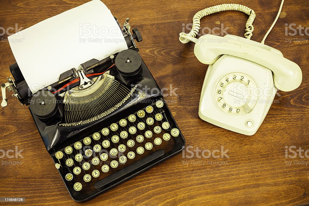 Vintage Typewriter with Old Telephone on Wooden Table stock photo