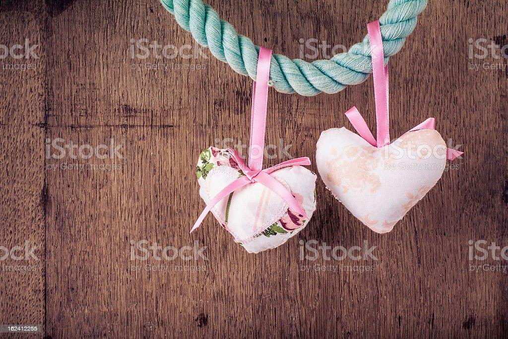 Vintage Valentine wooden background with hearts hanging on rope royalty-free stock photo