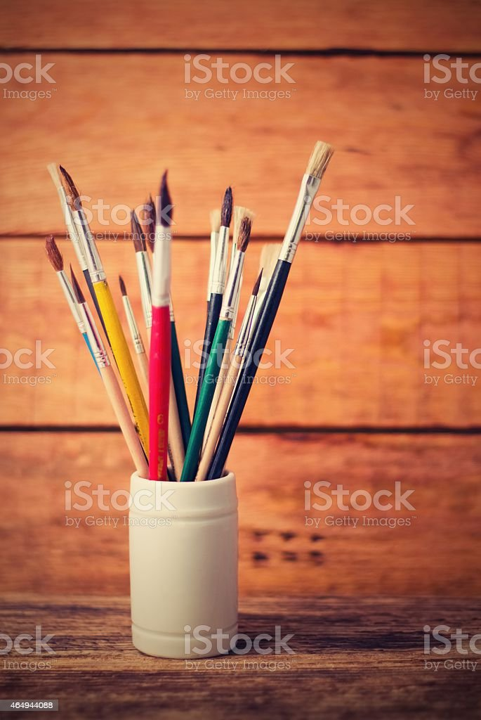 Vintage vertical retro photo of jar with paintbrushes stock photo