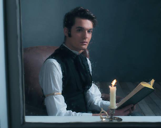 vintage victorian man sitting by rainy window reading book. - charles dickens weihnachtsgeschichte stock-fotos und bilder