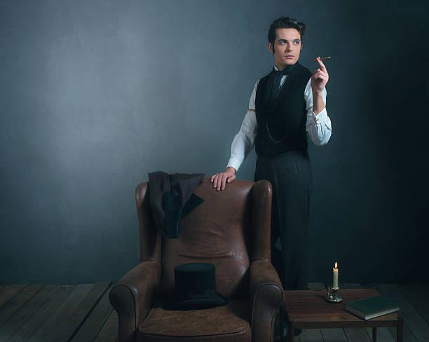 vintage victorian man standing next to chair smoking cigarette. - charles dickens weihnachtsgeschichte stock-fotos und bilder