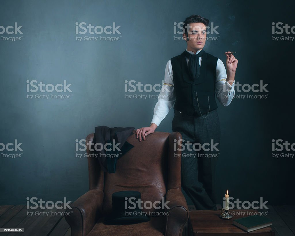 Vintage victorian man standing next to chair smoking cigarette. stock photo