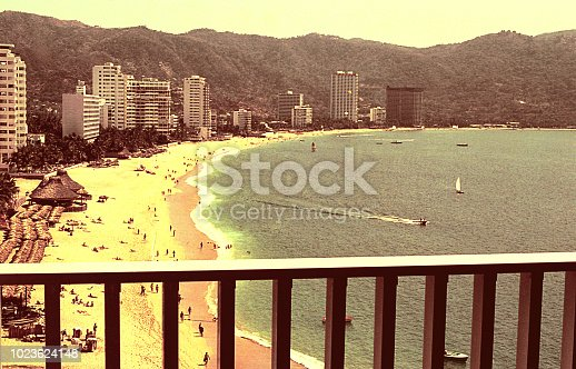 Vintage image of a beach in Acapulco viewed from a balcony.