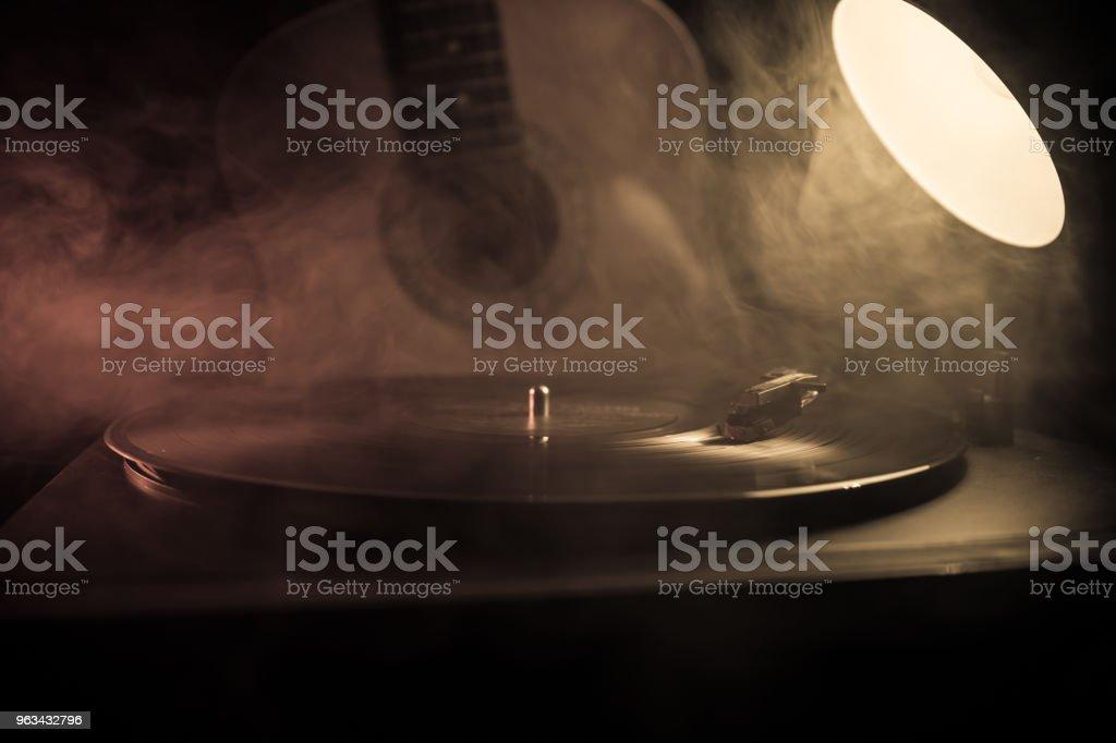 Disque de vinyle Vintage jouant à la guitare acoustique et joueur sur fond de fumée de feu orange. Concept de blues. Avec la voiture de jouet - Photo de Bleu libre de droits