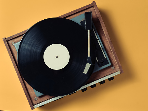 Vintage vinyl turntable with vinyl plate on a yellow pastel background. Entertainment 70s. Listen to music. Top view.