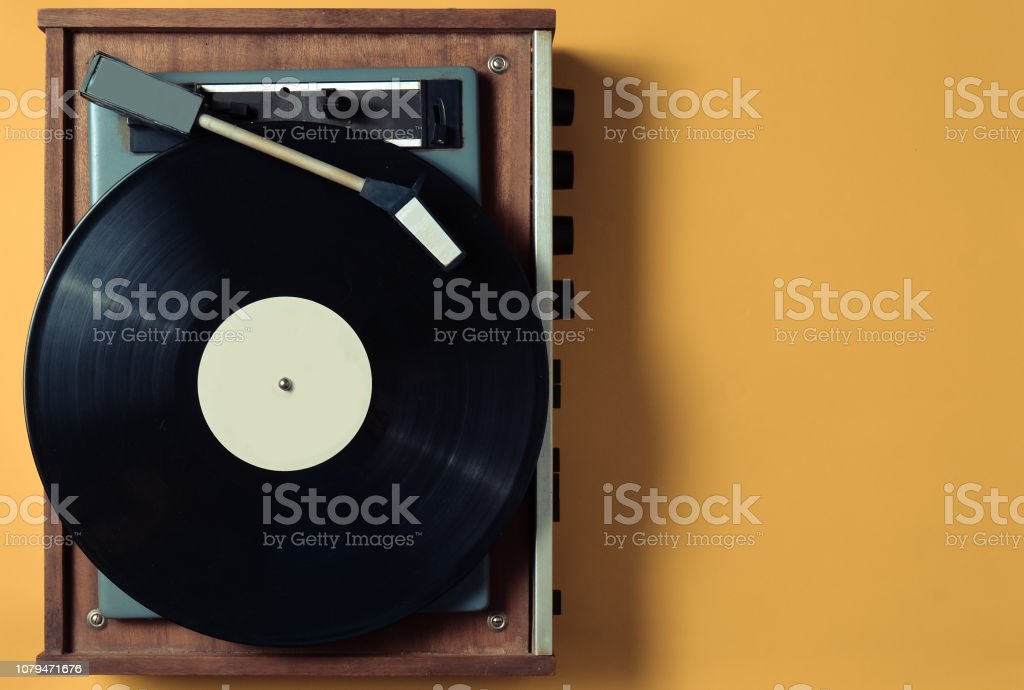 Vintage vinyl turntable with vinyl plate on a yellow pastel background. Entertainment 70s. Listen to music. Top view. – zdjęcie