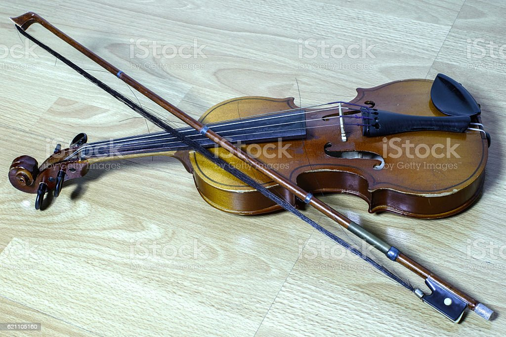 vintage violin with a bow lies on wooden bench stock photo