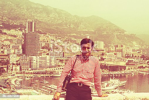 Vintage image from the seventies featuring a man standing against a view of the city of Cannes behind him.