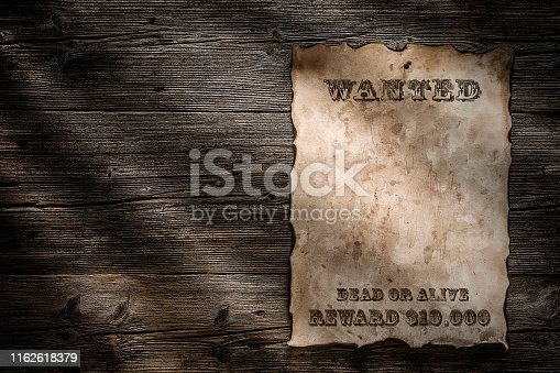 Vintage brown weathered wanted poster with burnt edges hanged at the right of a wood plank with a pushpin. The poster is at the right of an horizontal frame. Copy space available either on parchment and on the wood background. Text