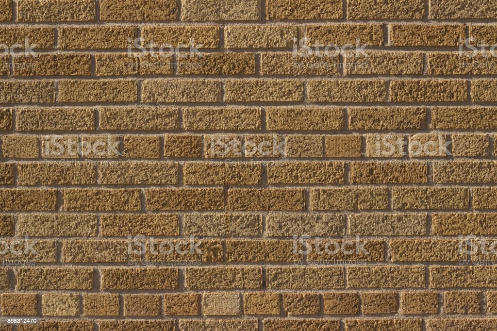 This brick wall background features lightly textured tan colored...