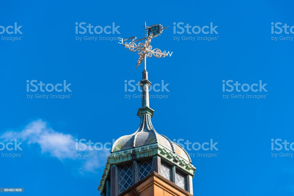 Vintage weatherclock on top of old building stock photo