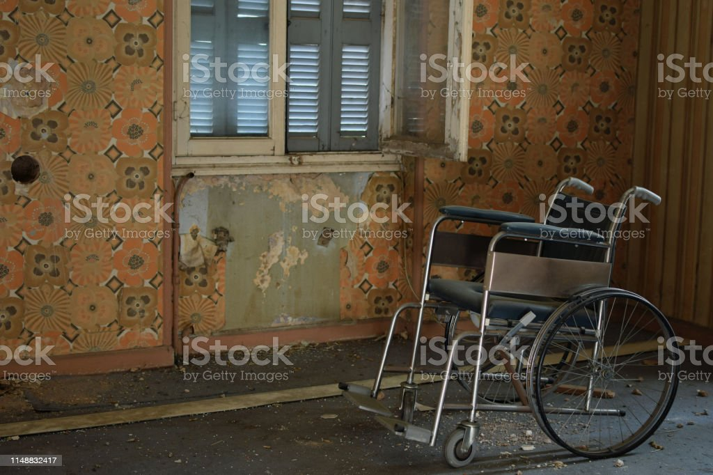Vintage wheelchair peeling wall and dusty floor in old house stock photo