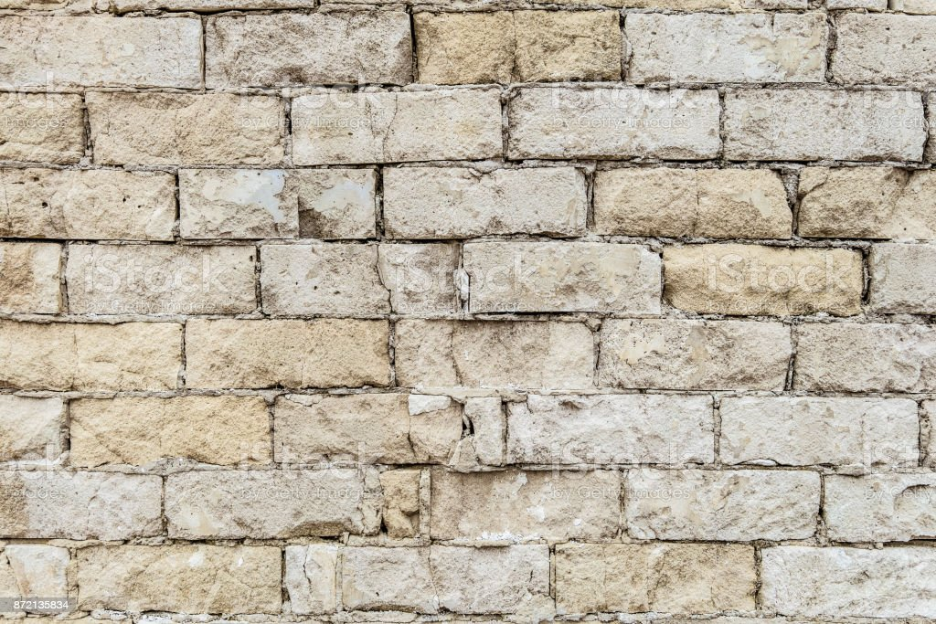 Vintage white brick wall texture. Background of an old weathered, thawed and cracked silicate brick wall. stock photo
