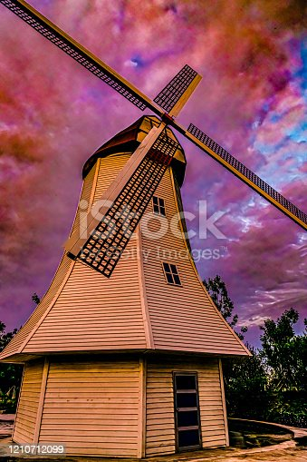 Vintage windmill and colorful clouds background