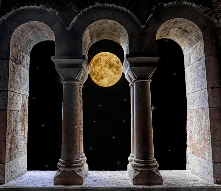 Beautiful background for the design of postcards and travel brochures. Colorful bright starry sky and stone arched window of romantic gothic ancient castle