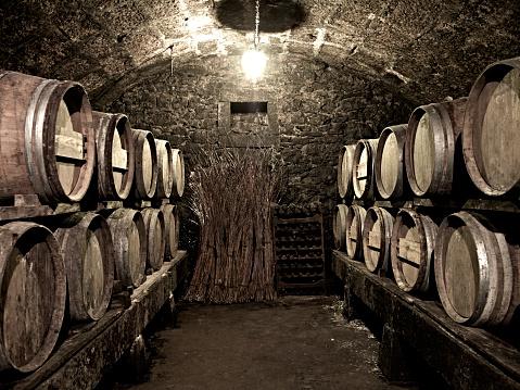 Vintage wine cellar with old wooden kegs