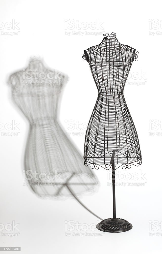 Vintage wire dress form with shadow against white background stock photo