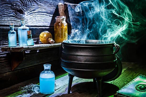 vintage witcher cauldron with blue smoke and potions for halloween - pfannen test stock-fotos und bilder