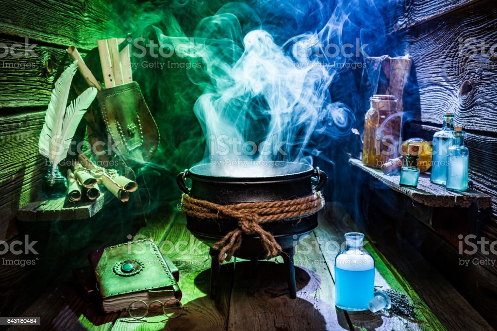 Vintage witcher cauldron with magic potions and books for Halloween stock photo