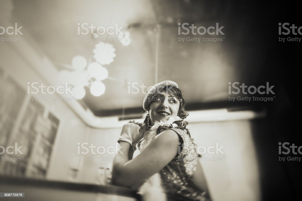 Vintage woman at bar counter drinking champagne and waiting stock photo