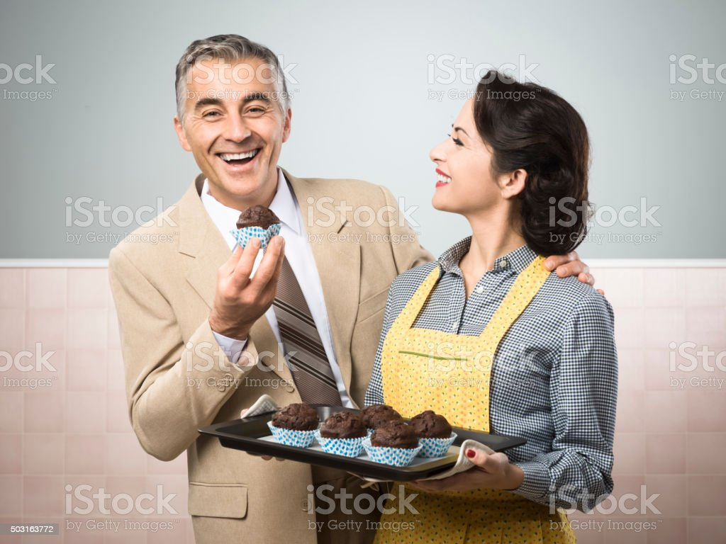 Vintage woman cooking muffins for her husband stock photo