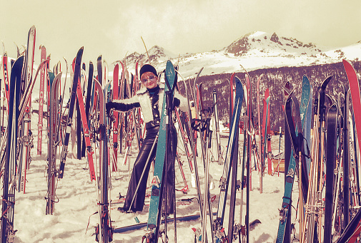 Vintage photo of a woman standing in the middle of skis in a ski resort