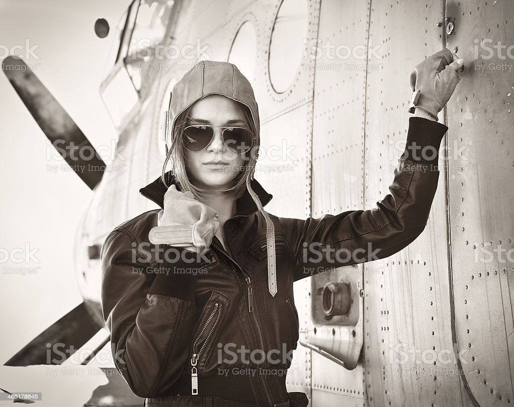 Vintage woman pilot in aviator sunglasses posing with plane stock photo