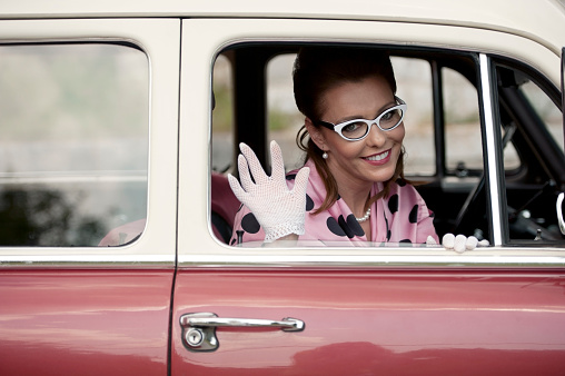 Beautiful adult woman who wearing vintage stayled clothings and accessories looking outdoors from the pasenger seat in the oldtimer car.