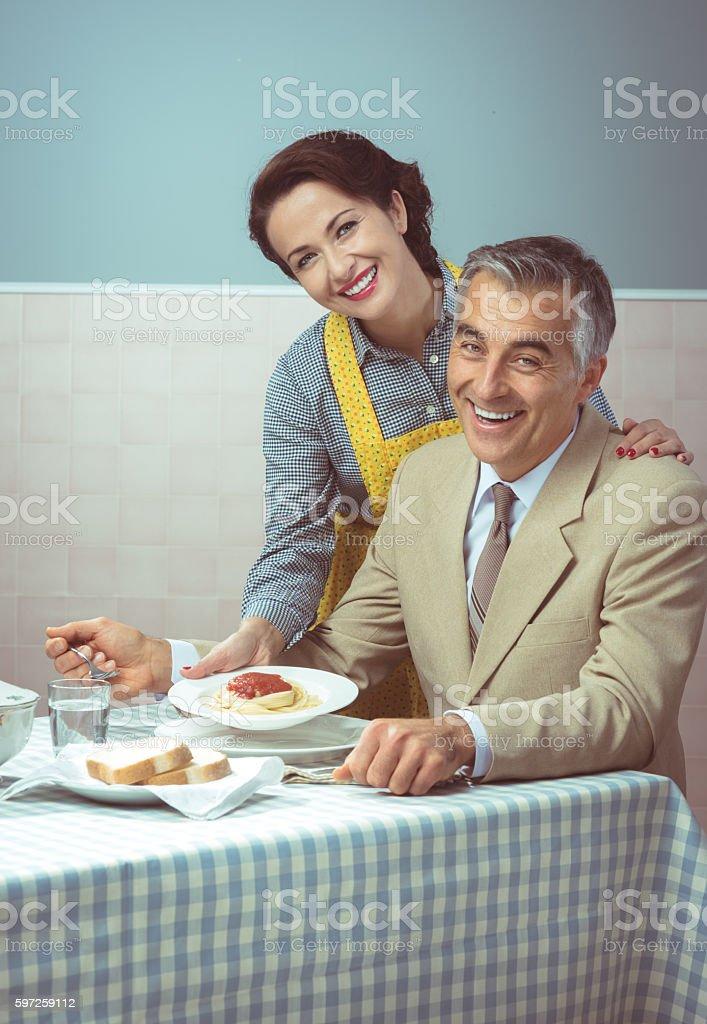 Vintage woman serving lunch to her husband stock photo
