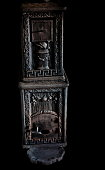 Vintage wood stove or fireplace from the late 1900s made in black cast iron with ornaments. Isolated on black.