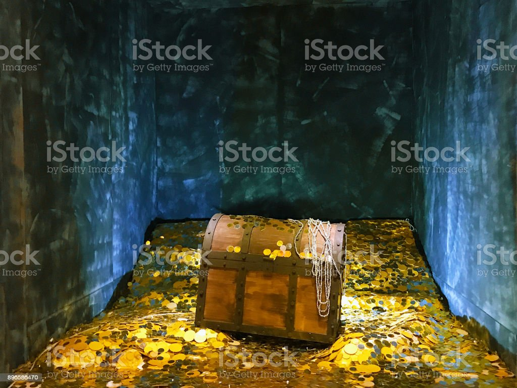 A vintage wood treasure box with shinny gold metal and golden coin. stock photo