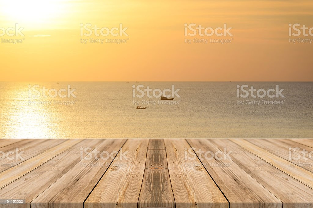 Vintage wooden board empty table sea and sky sunset background. stock photo