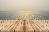 istock Vintage wooden board empty table sea and sky sunset background. 494154448