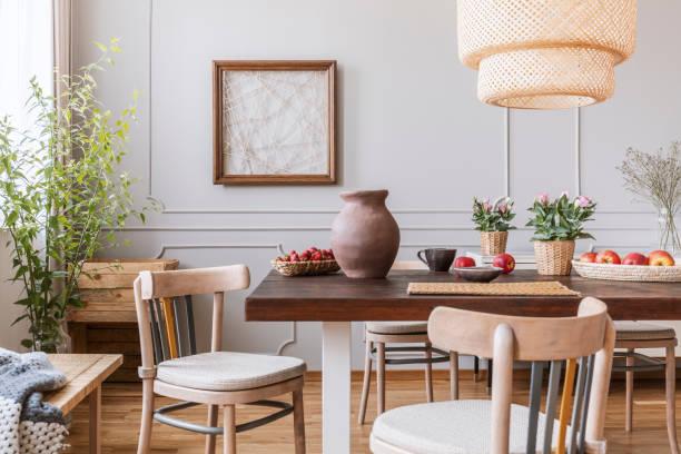 vintage holzstühlen im wohnzimmer mit langer tisch mit erdbeeren, äpfel, vase und blumen drauf, echtes foto - landhausstil küche stock-fotos und bilder