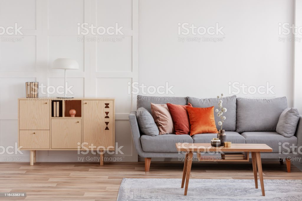 Vintage wooden commode next to grey Scandinavian sofa with pillows Vintage wooden commode next to grey Scandinavian sofa with pillows Apartment Stock Photo