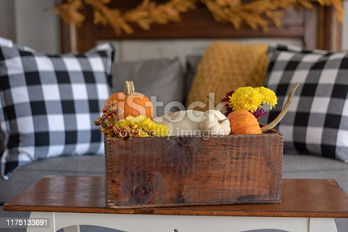 Using a vintage wooden crate to hold colorful autumn flowers and pumpkins - fall decorations for the home