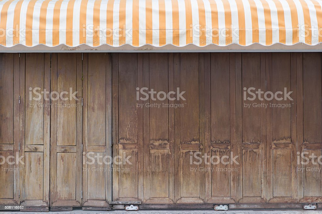 Vintage wooden gate with yellow stripe awning stock photo