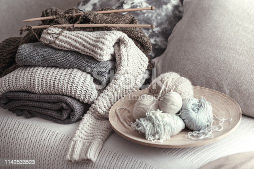 Vintage wooden knitting needles and threads for knitting on a cozy sofa with pillows and sweaters. Still life photo. The concept of comfort